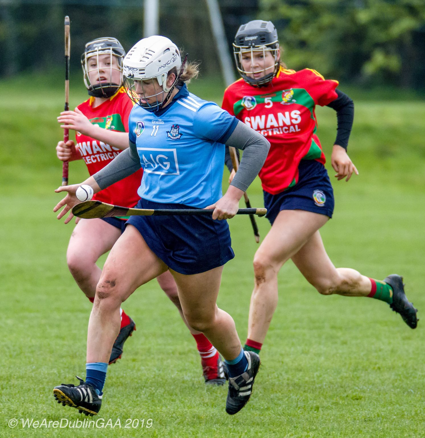 A Dublin Intermediate Camogie Player In a sky blue jersey, navy skort and white helmet raced away from two Carlow players in red jerseys and navy skorts during the relegation playoff game which Dublin won to secure their Division 2 status