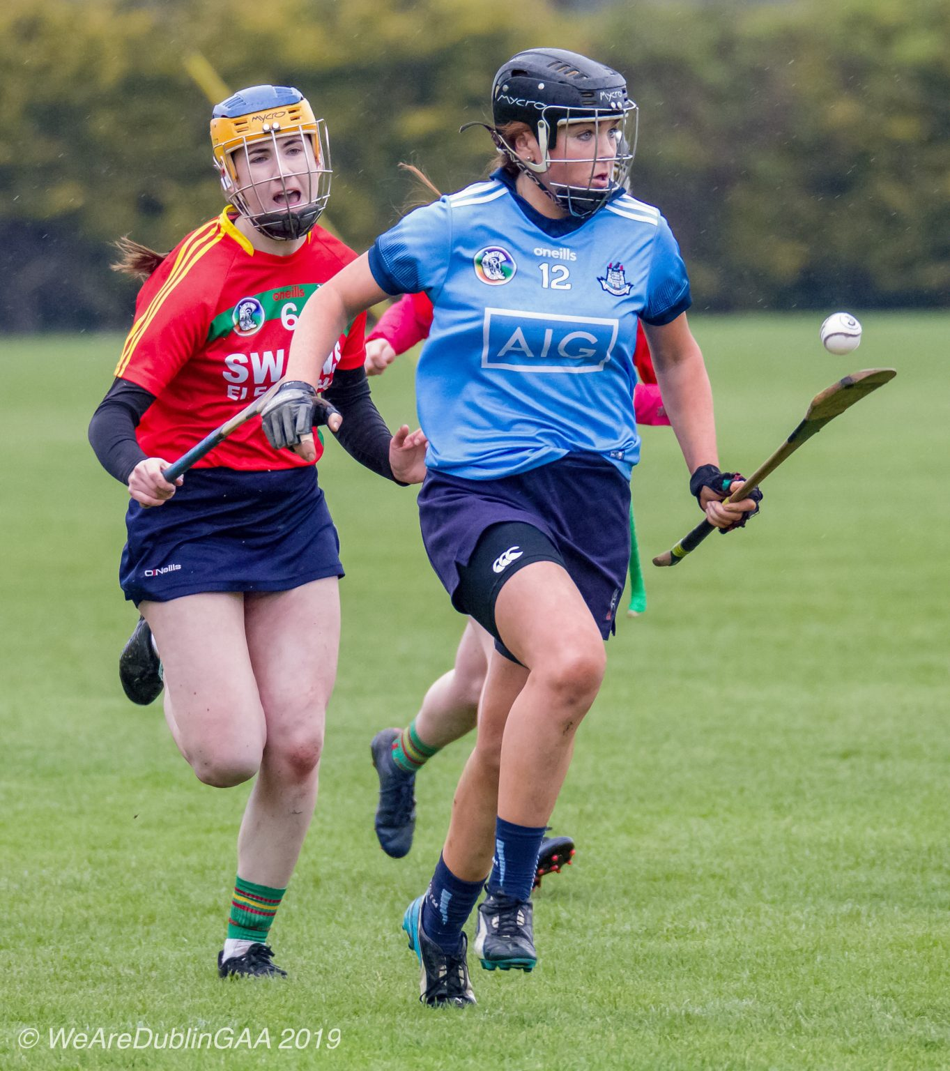 Dublin Camogie Intermediate Player In a sky blue jersey, navy skort and black helmet raced away from a Carlow player in a red jersey with green and yellow stripes across the front and sleeves, navy skort and black and white helmet.