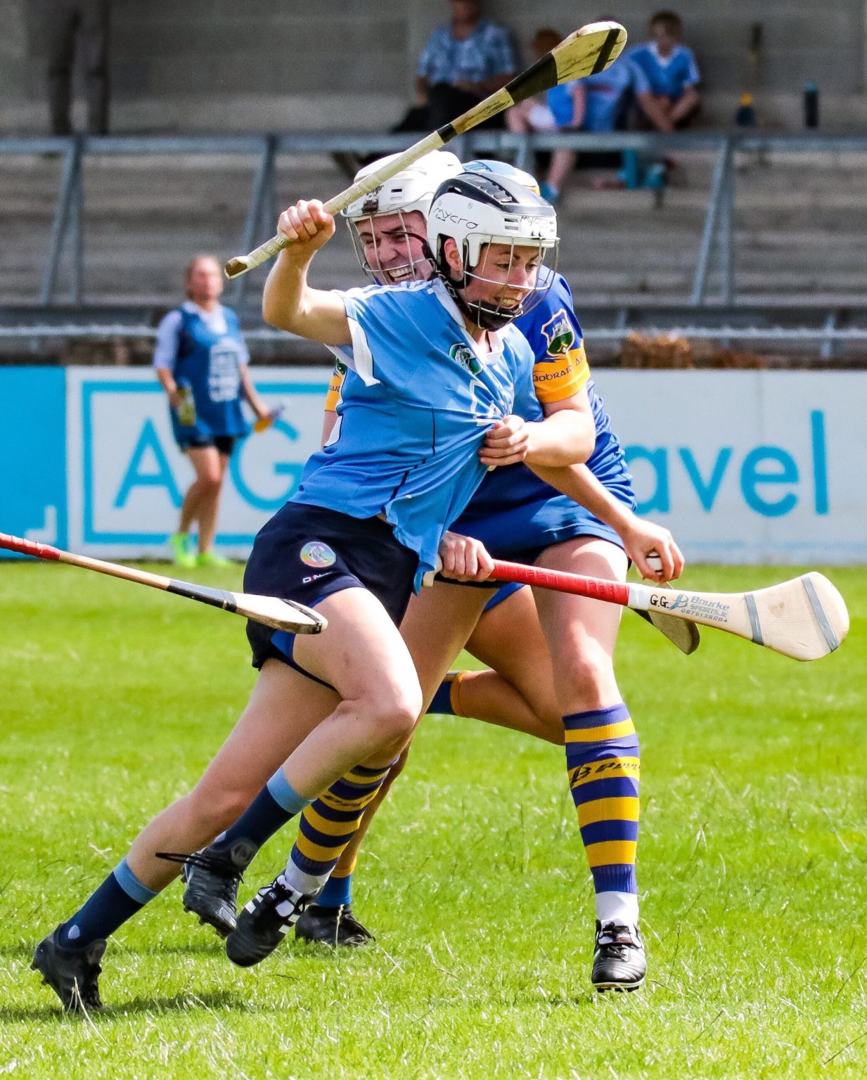 Dublin camogie player in a sky blue jersey, navy skort and black and white helmet has her jersey held by a Tipperary player in a dark blue jersey with yellow trim, dark blue skort and white helmet, players have called for rule changes particularly the physical contact rule