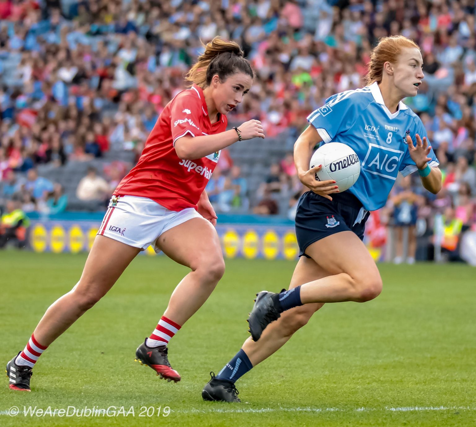 A Dublin Ladies Footballer in a sky blue jersey and navy shorts runs away with the ball from a Cork player in a red jersey and white shorts, the venue for the sides league semi final has been confirmed