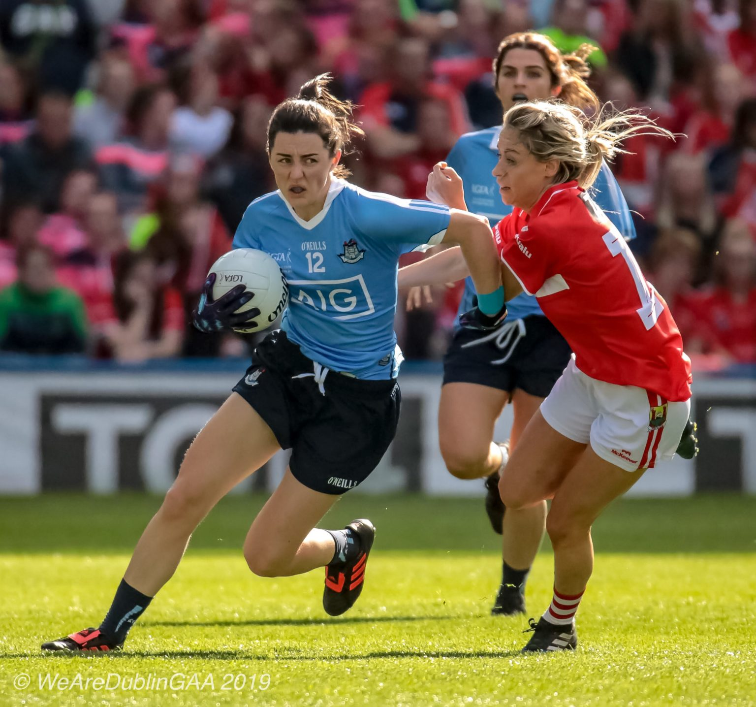 Dublin Ladies Footballer in a sky blue jersey and navy shorts is tackled by a Cork player in a Red Jersey and white shorts both sides meet this weekend in the Lidl NFL Semi Final