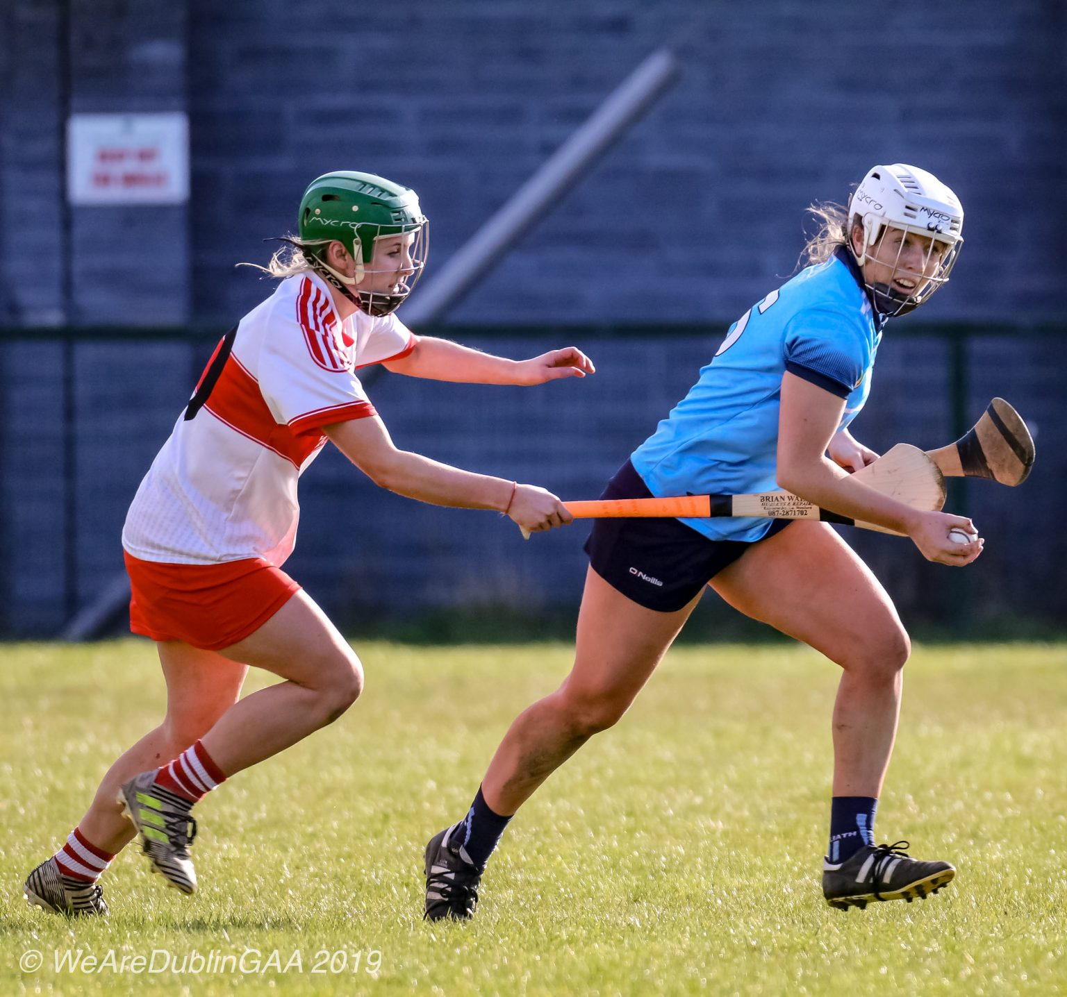 Dublin Camogie player in a sky blue jersey, navy skort and white helmet gets away from the tackle of a Derry player in a white jersey with band across the chest, red skort and green helmet image is used to advertise Féile