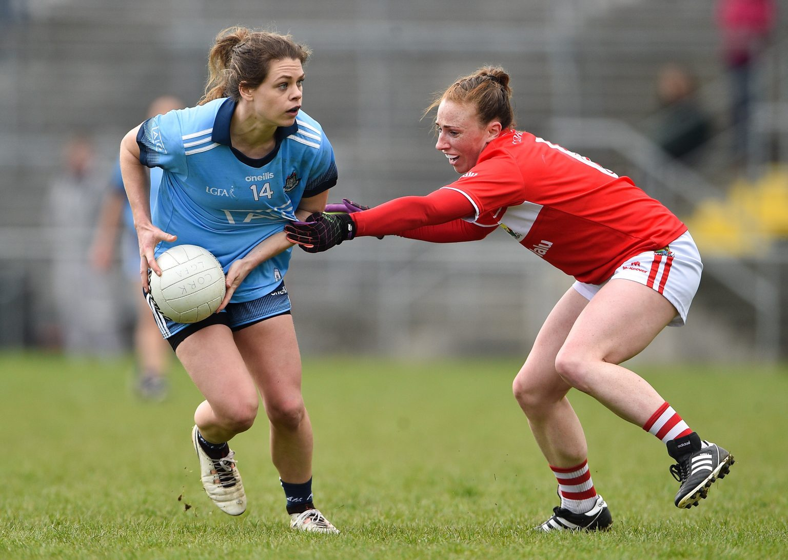Dublin Ladies Footballer in a sky blue jersey and navy shorts evades the tackle of a Cork player in a red jersey and white shorts with red stripes down the side, Cork won the game but both sides meet again in two weeks in the Lidl NFL semi final