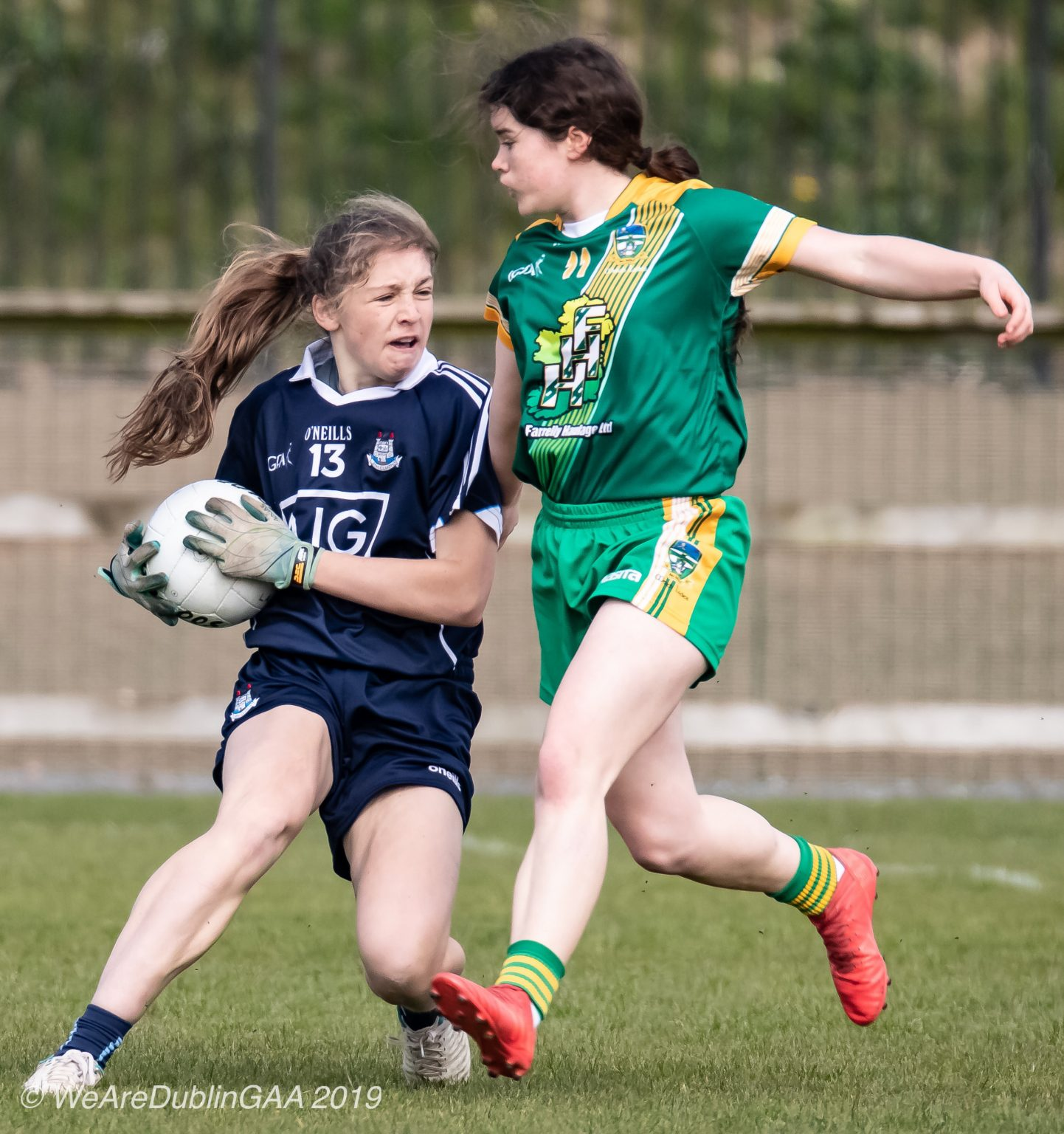 Dublin Ladies footballer in a navy jersey and navy shorts is tackled by a Meath player in a green jersey with yellow stripes across the front and green shorts both sides meet in the Leinster U16 Championship Final.