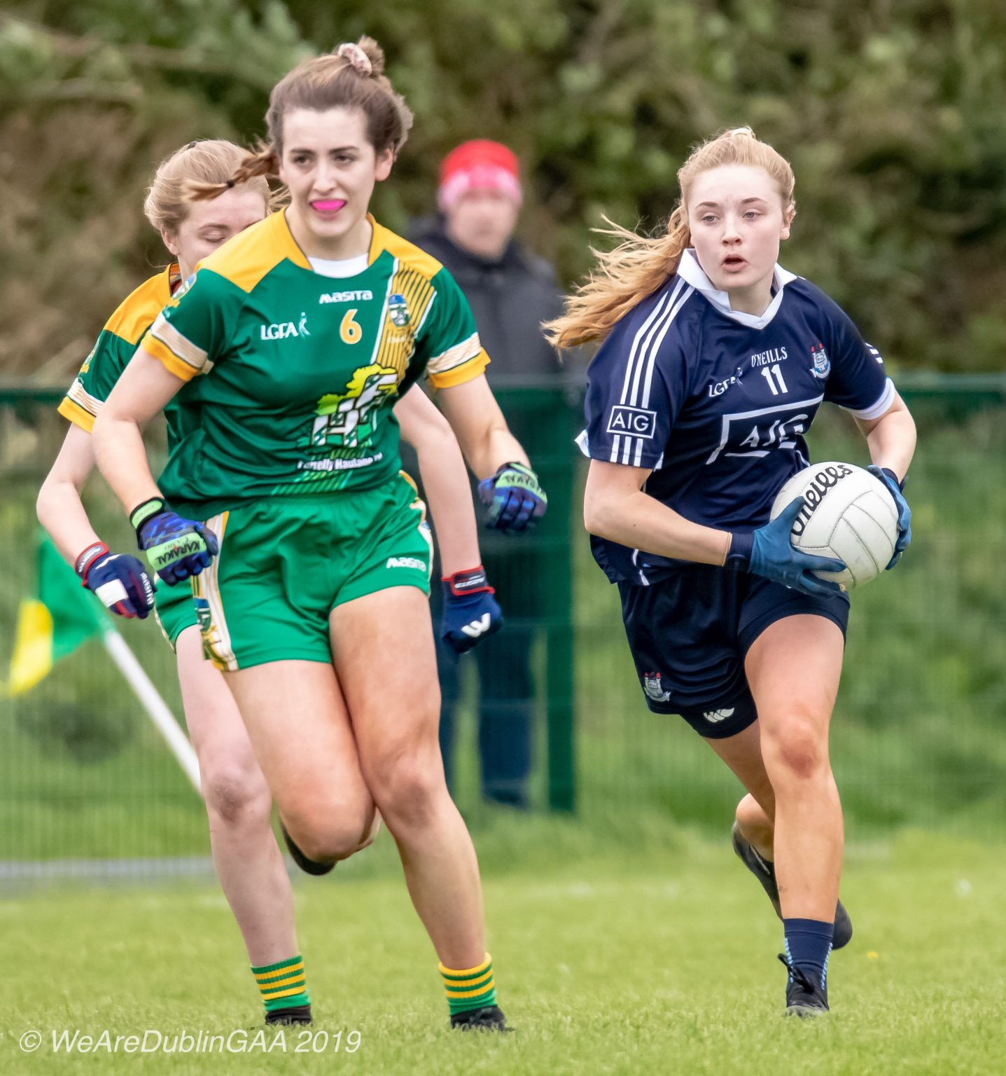 Dublin Ladies Footballer In a Navy Jersey and navy shorts raced away from two Meath players in green jersey with yellow stripes across the front and green shorts, Meath won the game to claim the Leinster U16 Championship title