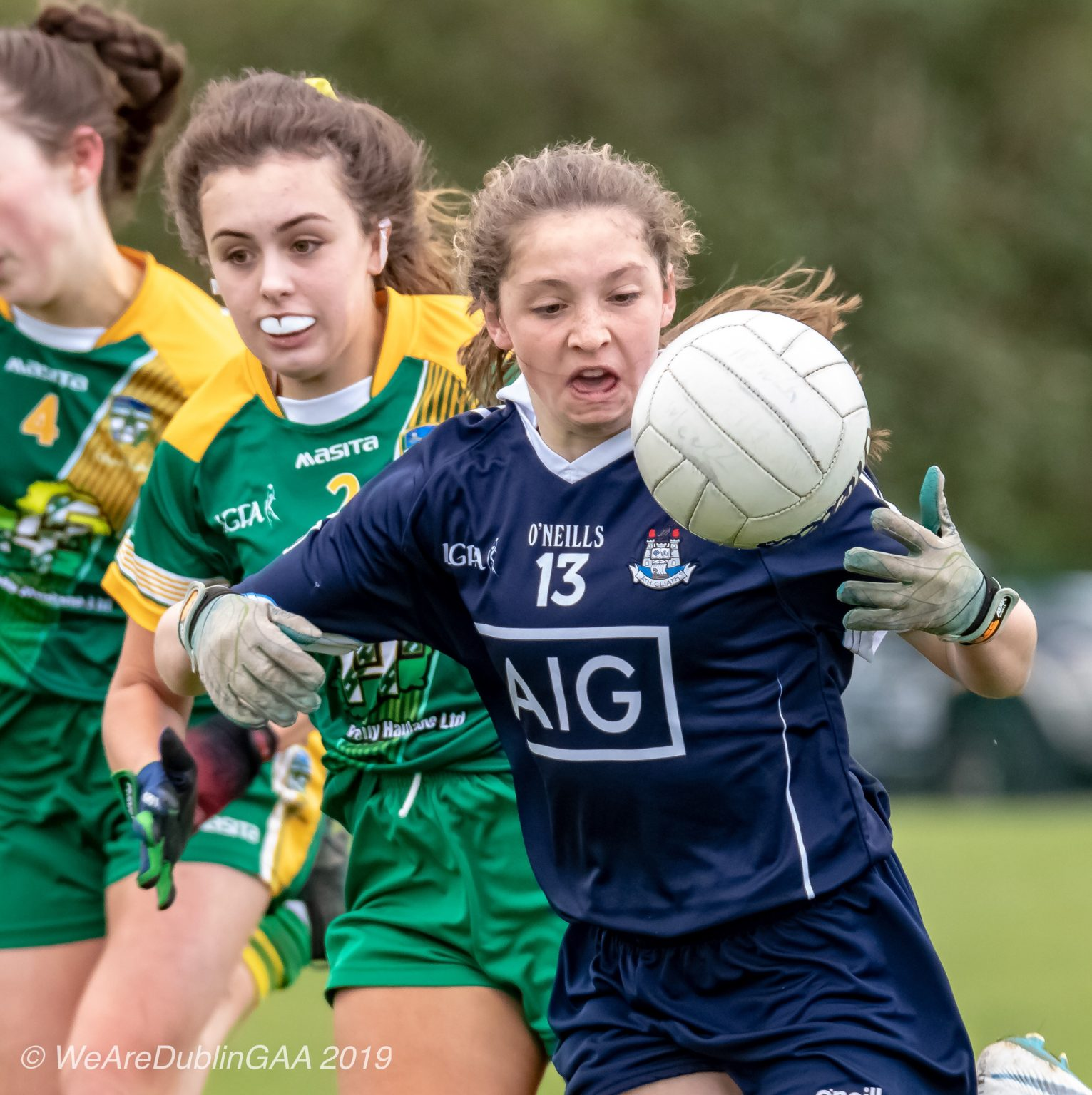 Dublin Ladies Footballer In a Navy Jersey and navy shorts catches the ball while being tackled by a Meath player in a green jersey with yellow stripes across the front and green shorts, Meath won the Leinster U16 championship title