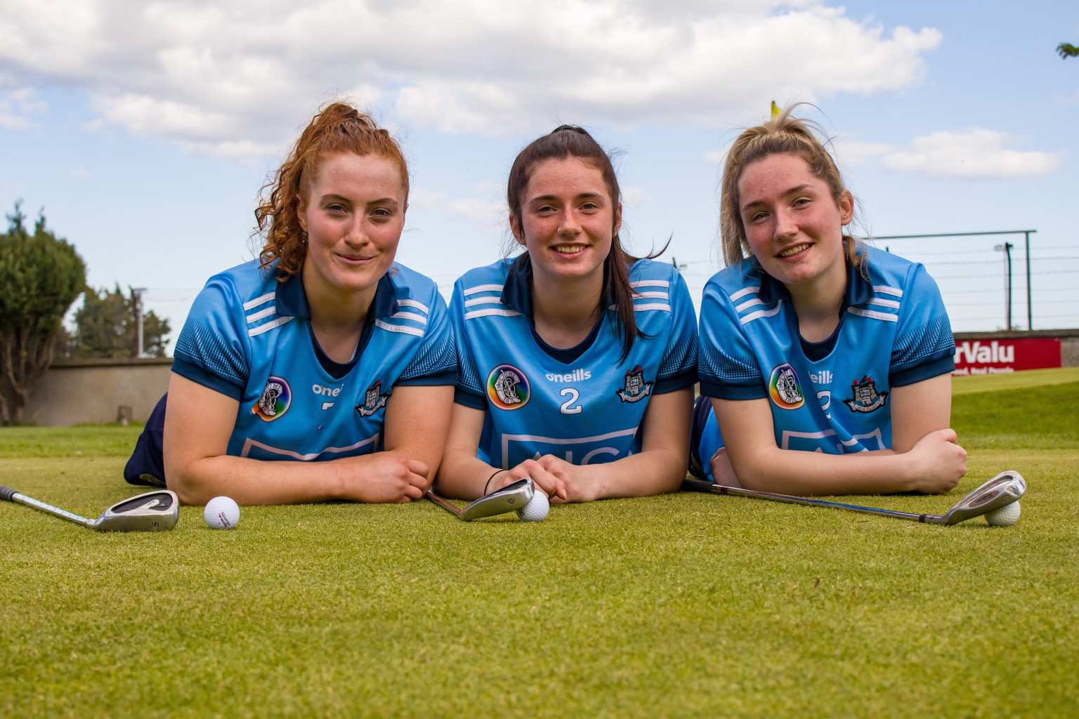 Three Dublin Camogie Players In sky blue jerseys lying down on a golf green with golf clubs and balls in front of them to advertise the Dublin Camogie weekly notes which include info on the camogie Golf Classic and Dublin Poc Fada
