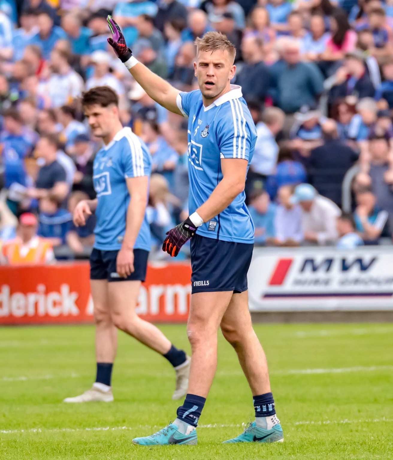 Dublin footballer Jonny Cooper in a Sky Blue Jersey and navy shorts with his hand raised in the air