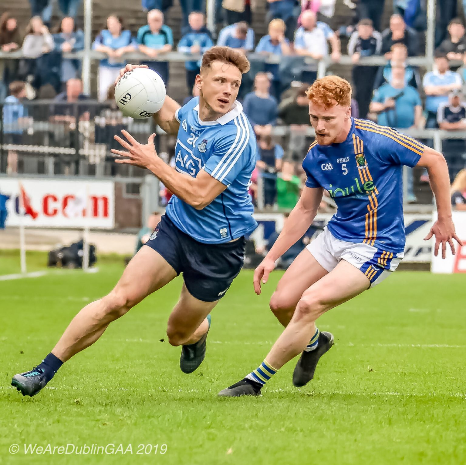 Dublin footballer Paul Flynn in a sky blue jersey and navy shorts gets away from a Wicklow player in a dark blue jersey with yellow stripes down the front and white shorts with blue and yellow trim.