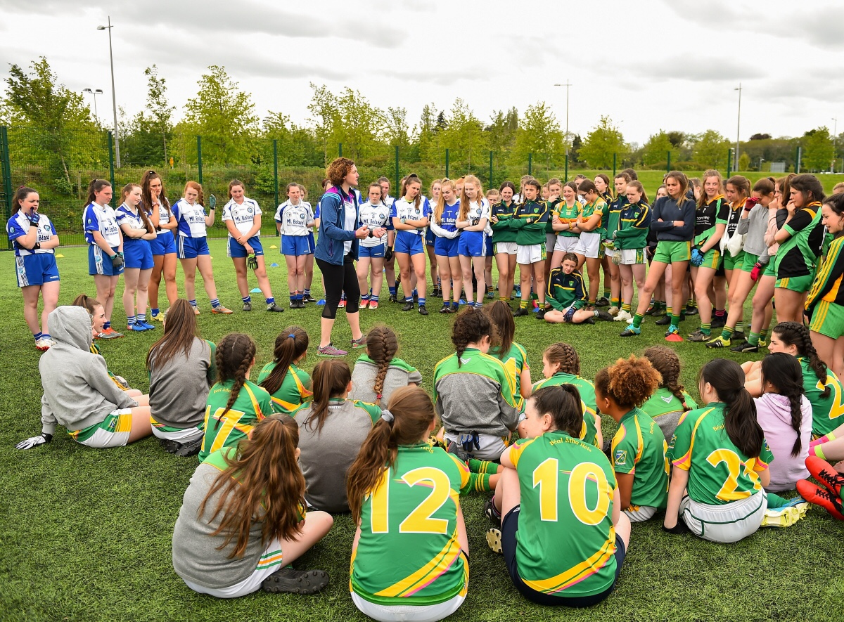 A large group of ladies Footballers gather in a circle around a coach during the 2019 Gaelic4Teens Programme