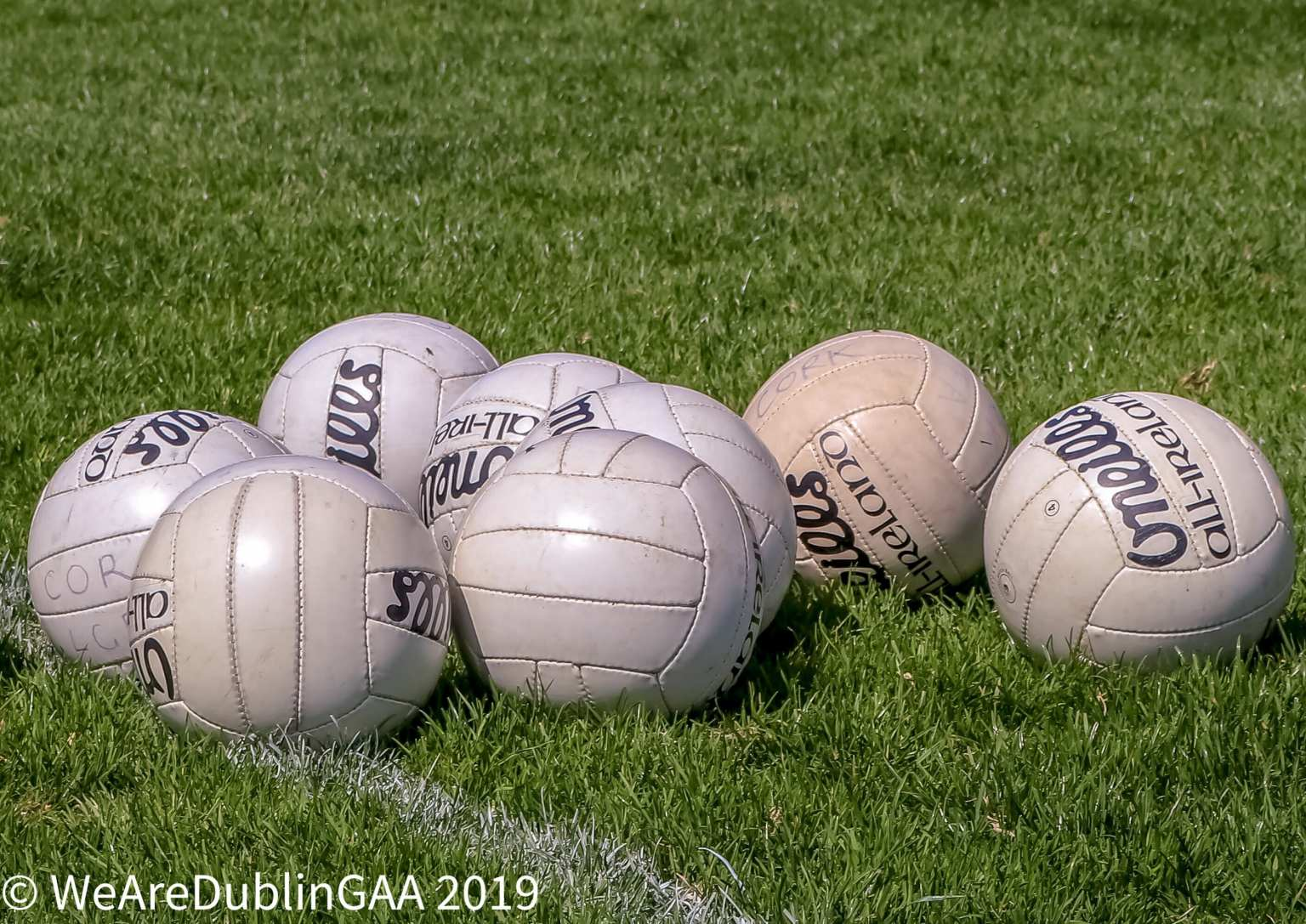 Eight Gaelic Footballs on a pitch to advertise the LGFA All Ireland Club Seven A Side Tournament