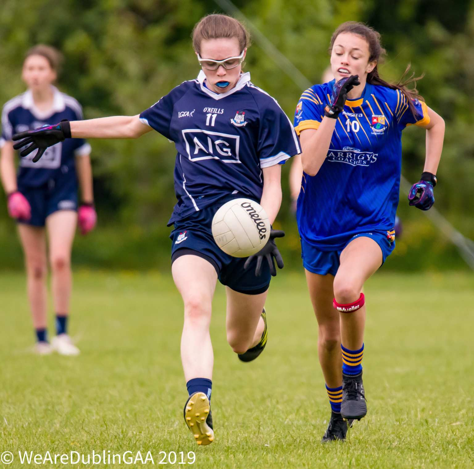 Dublin Ladies footballer in a navy jersey and navy shorts breaks away from a Longford player in a dark blue jersey and dark blue shorts during the U14 All Ireland quarter Final which Longford won with a late goal