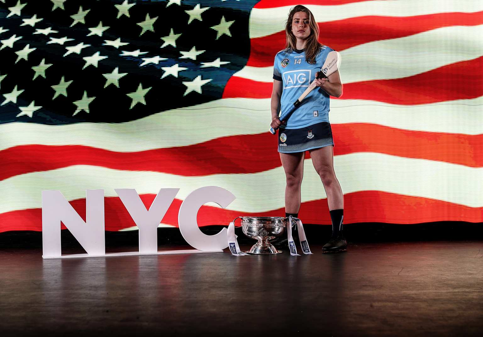 Dublin Senior Camogie Player Aisling Maher pictured at the Camogie All Ireland Championships launch with an American flag behind her and the O'Duffy Cup on the floor beside her with the a NYC prop on the floor because New York was announced as the destination for this year's All-Stars tour.