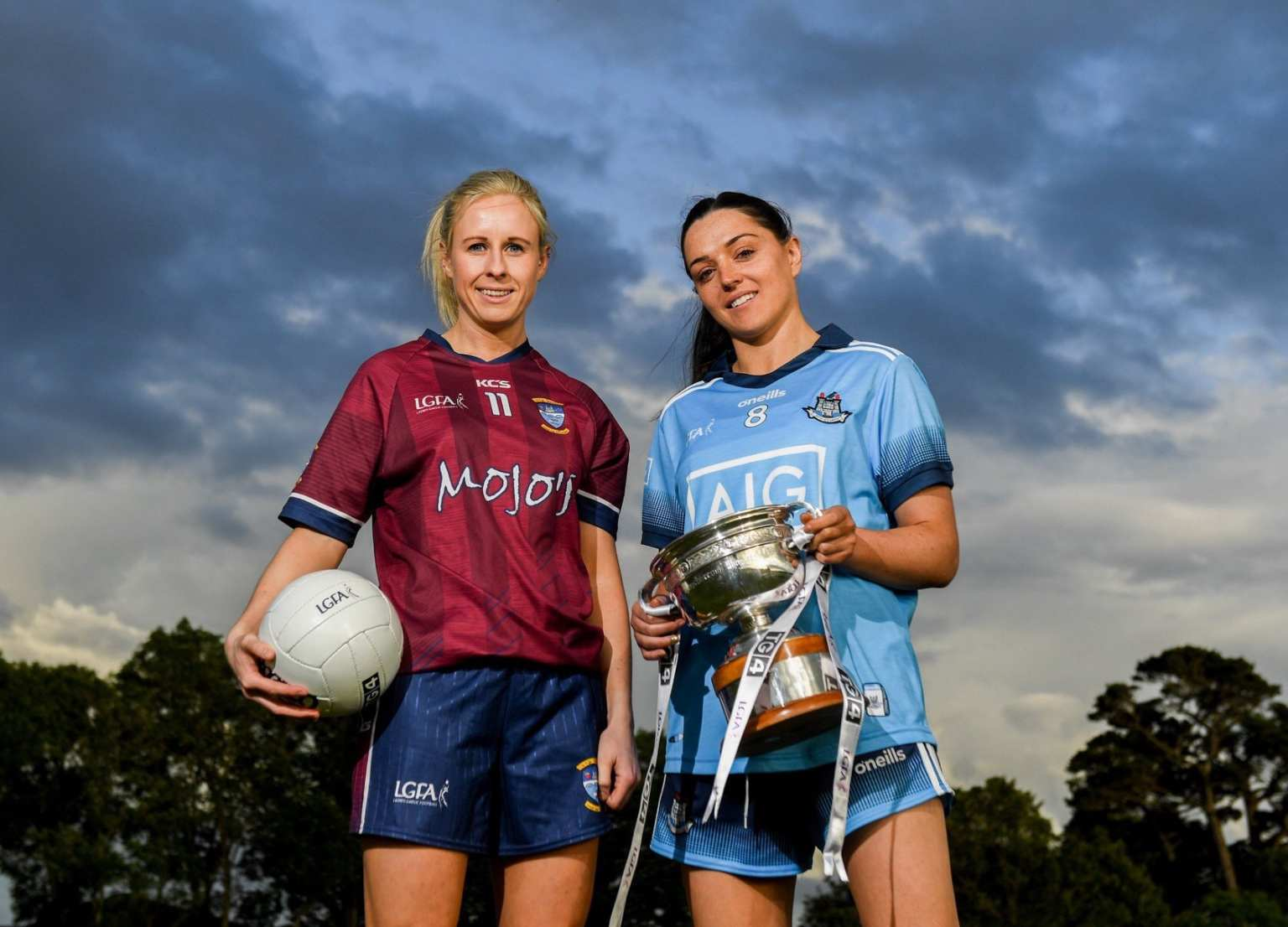 A Westmeath and Dublin Ladies footballer holding a ball and the Leinster trophy both sides meet in this weekend's Leinster Senior Final