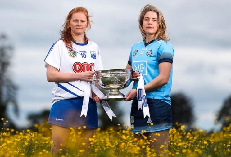 A Waterford player and a Player from the Dublin Senior Camogie Team holding the O'Duffy Cup in a meadow of yellow flowers