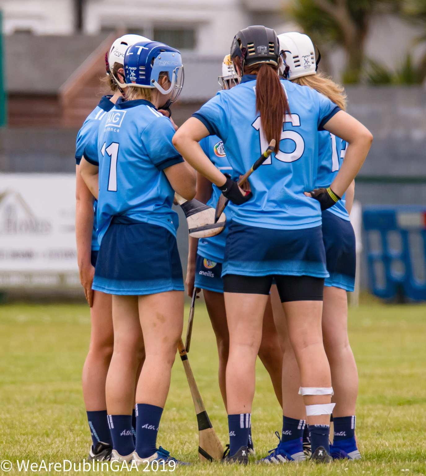 A group of Dublin Camogie players gather in a circle to talk during a Intermediate championship game.
