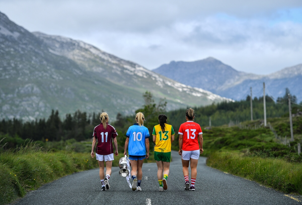 Four ladies footballers walking along a country road with their backs to the camera at the photo shoot for the 2019 TG4 All Ireland Series