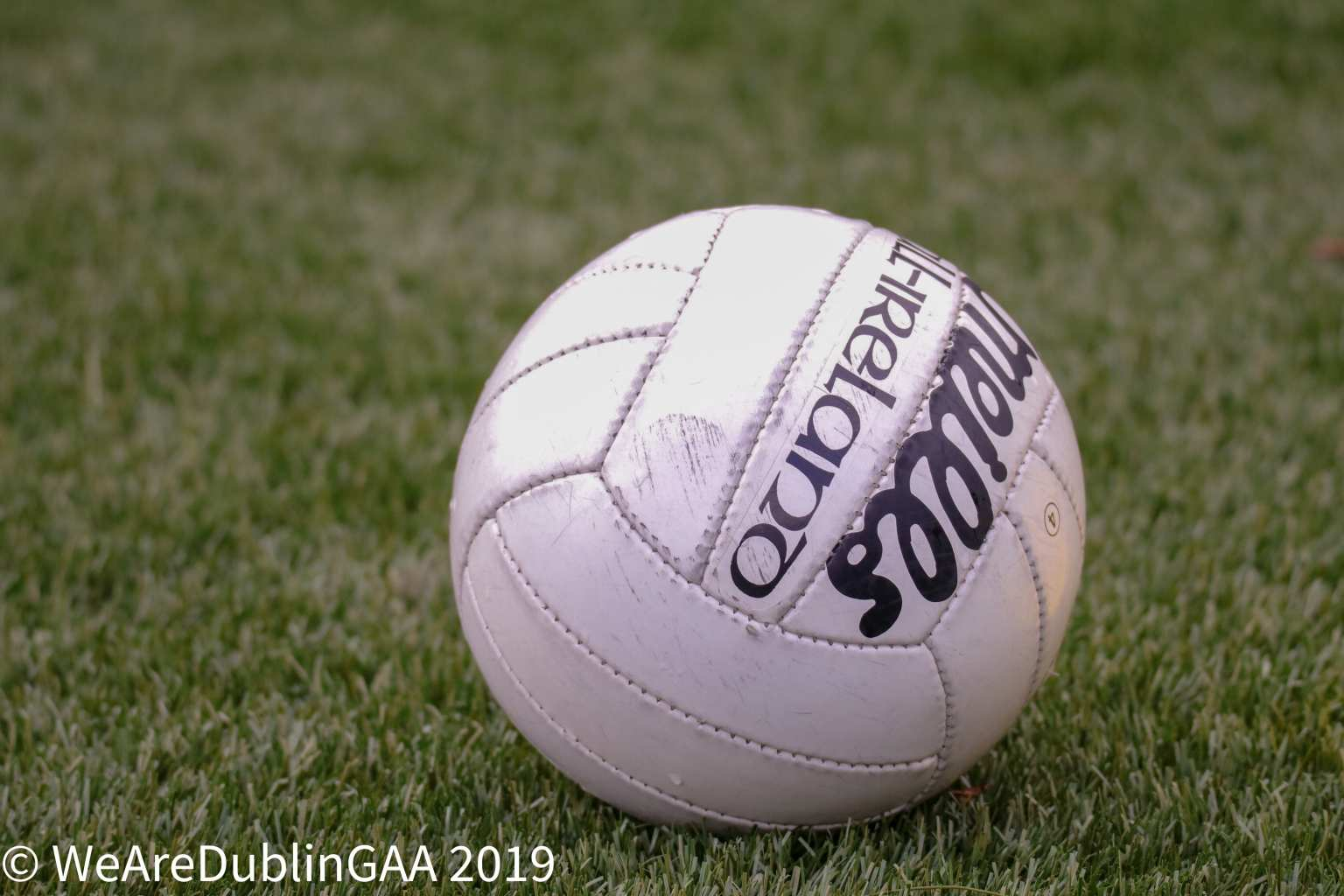 A white Gaelic football on a grass pitch to signify the Dublin LGFA club results.
