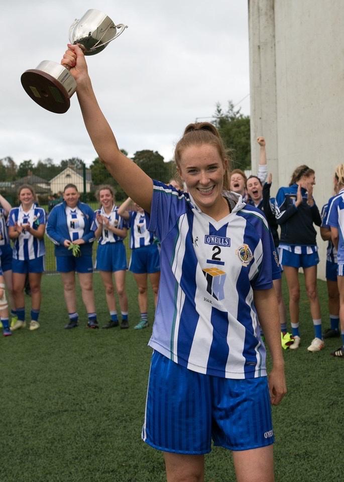 Ballyboden St Endas Ladies Football Captain raises the Junior B trophy into the air.