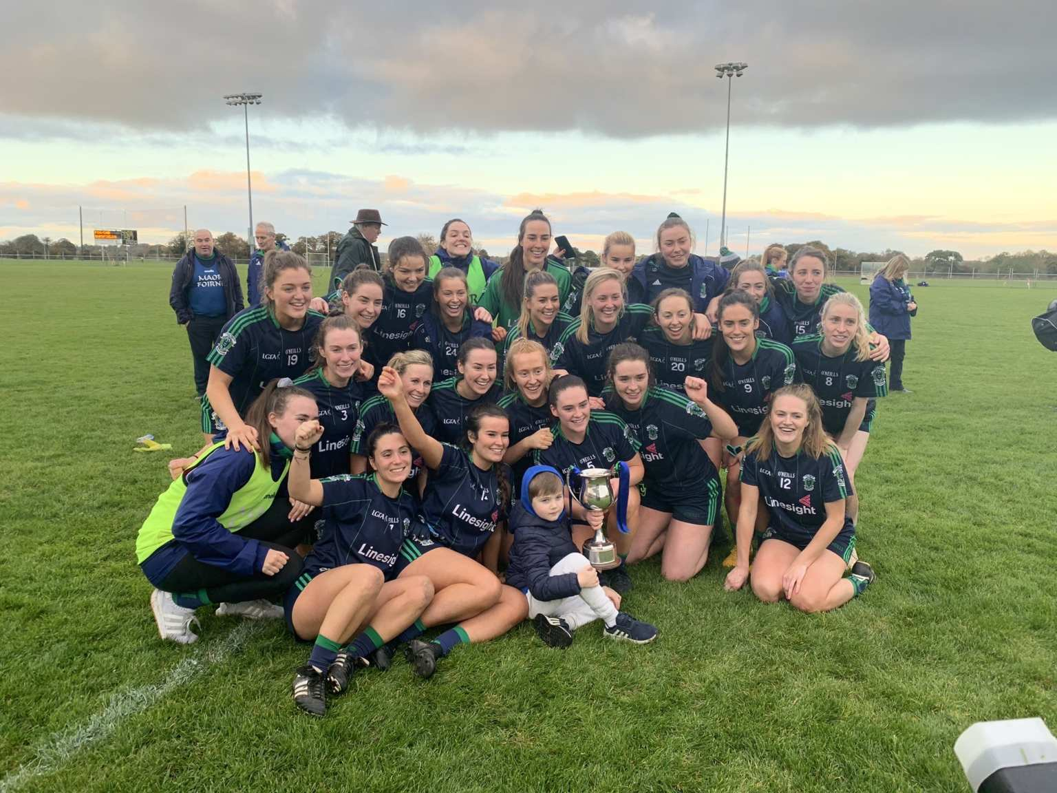 Foxrock Cabinteely players celebrating on the pitch after winning their Fifth Leinster Senior ladies Footballers title one a row.