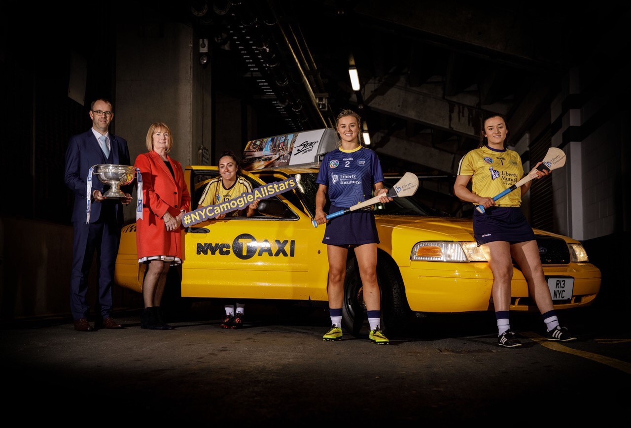 Seán Brett From Liberty Insurance, Kathleen Woods president of the Camogie Association and Amy O'Connor, Grace Walsh and Sarah Healy standing next to a New York taxi at a media event for the All Stars trip to New York