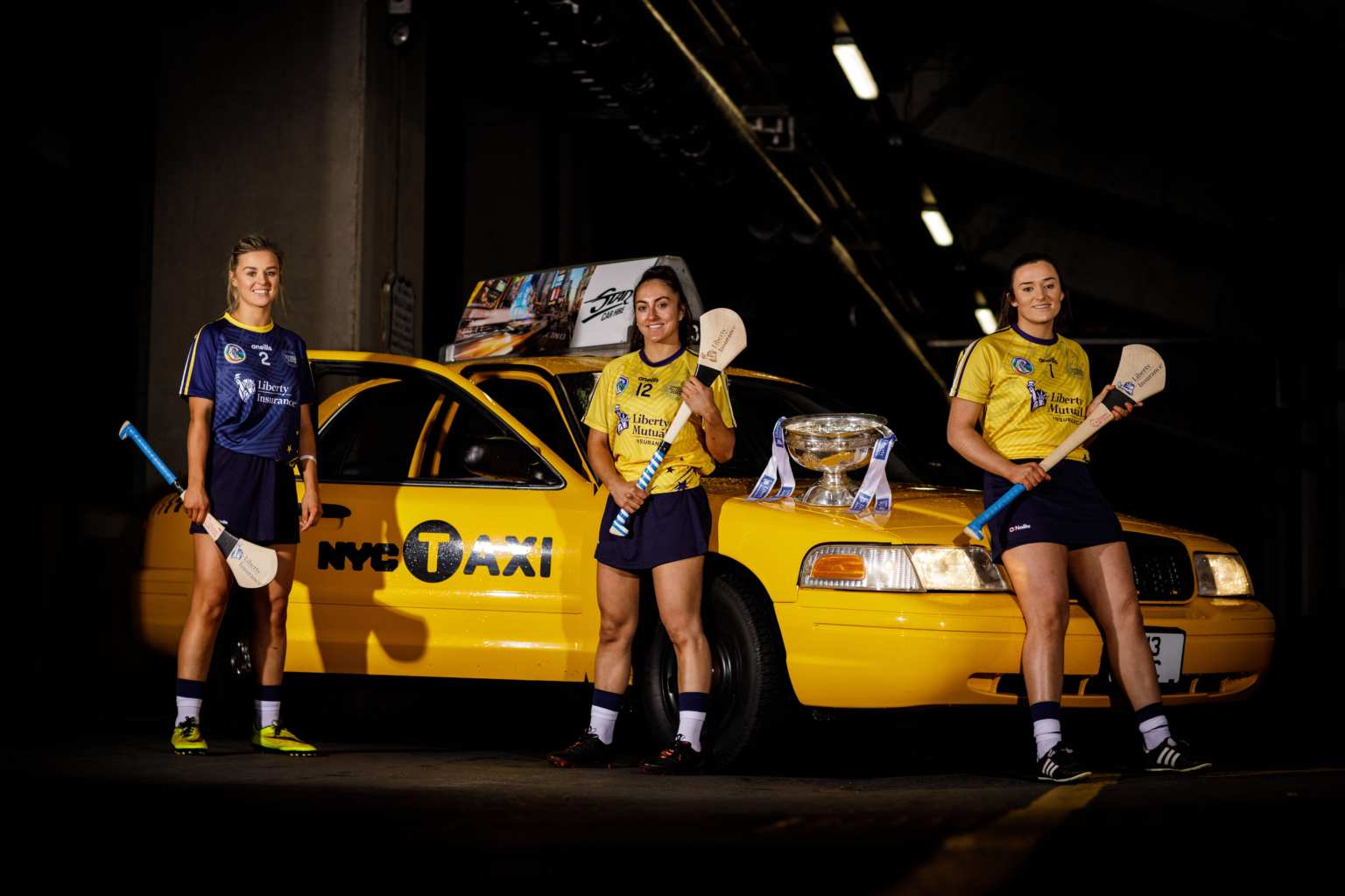Three members of the Camogie All Stars squad with a New York Taxi to signify their trip to New York for an exhibition match.