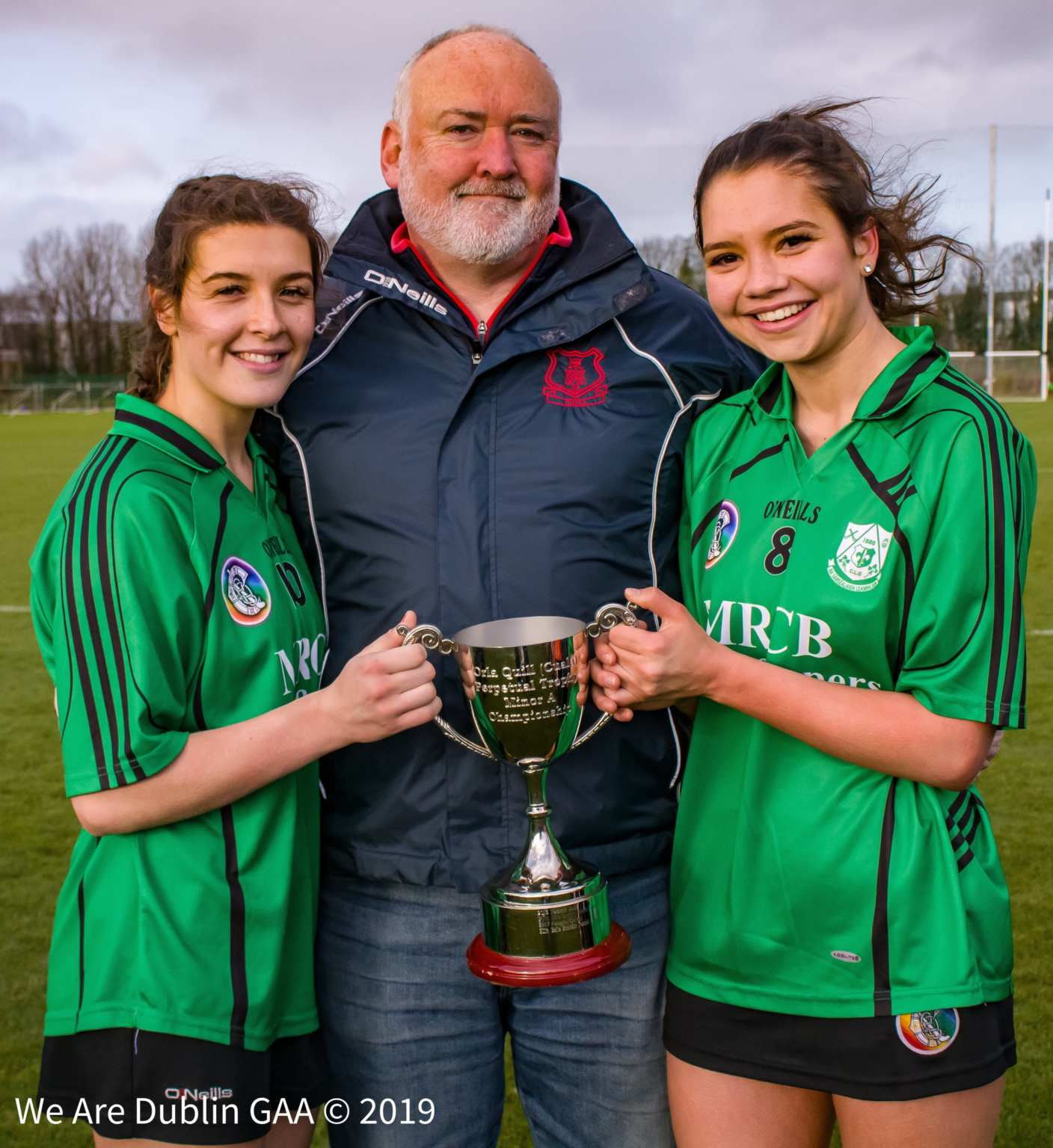 Fintan Quill (Centre) presents the Orla Quill Trophy makes in honour of his late daughter to the winning Lucan Sarsfields joint captains Laura Quinn (L) Aoife Mahon (R)