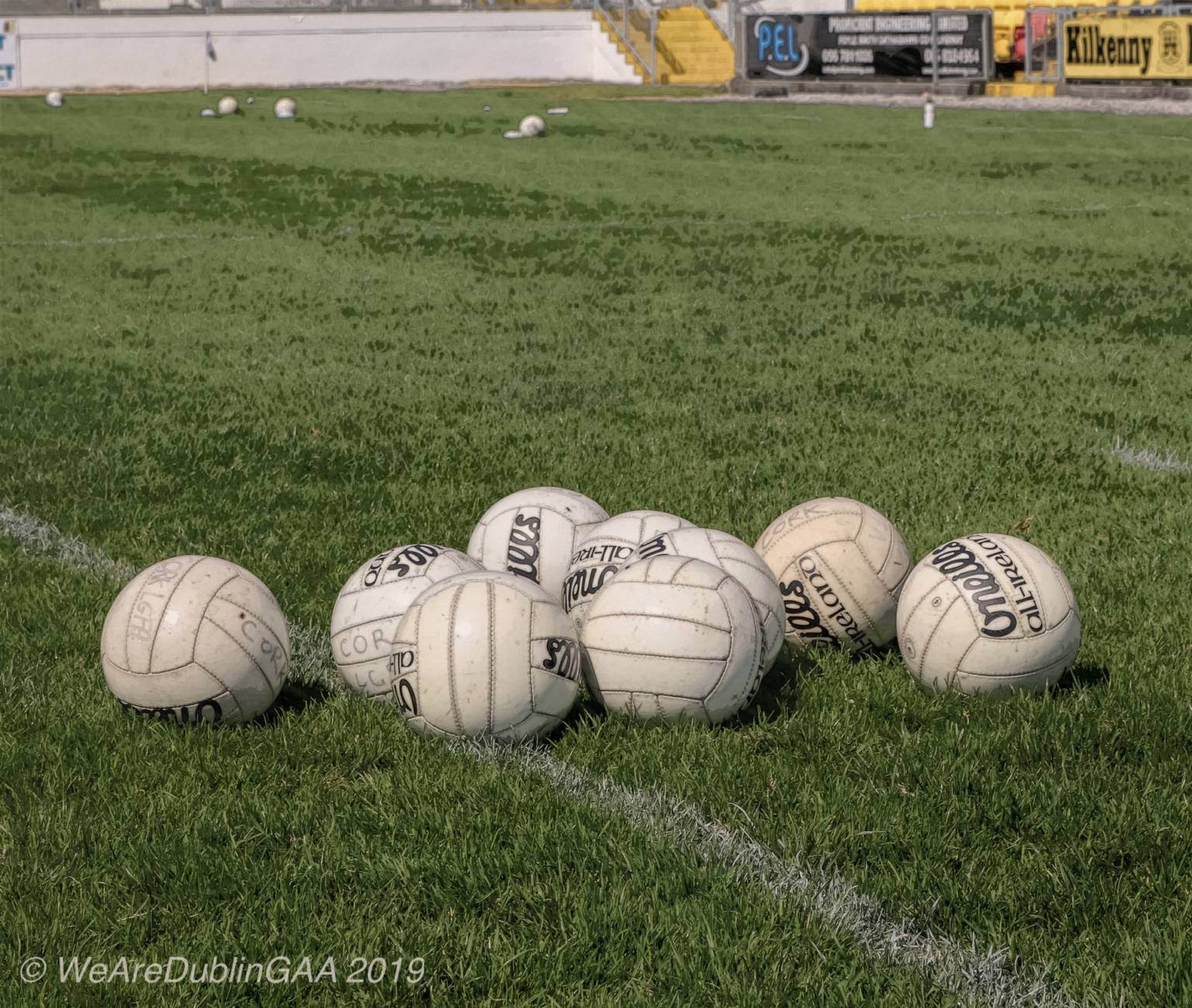 Gaelic Footballs sitting on a grass pitch to signify that the start of the All Ireland championship has been delayed due to Covid-19