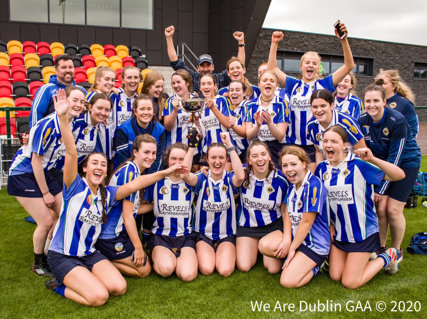 Ballyboden St Endas players celebrate on the pitch with the cup after winning the Intermediate 2 championship title.