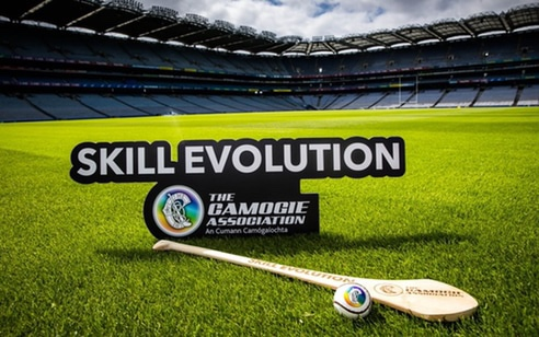 A hurl and sliotar sit on the grass of Croke Park with a sign which says Skill Evolution which was launched this week, Skill Evolution is a suite of videos which gives a modern look at the technical skills of Camogie.