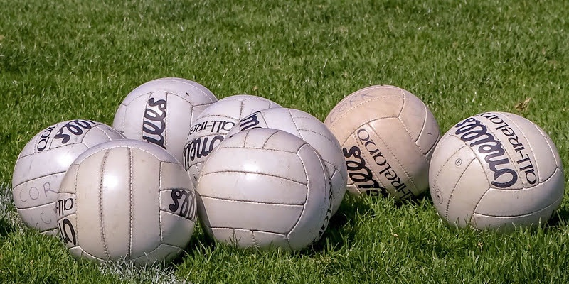 Seven ladies Gaelic footballs on a pitch with the Go-Ahead Junior Championship and Shield finals taking place this evening